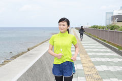Young woman jogging by the sea Stock Image