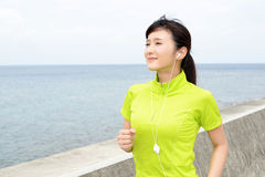 Young woman jogging by the sea Royalty Free Stock Images