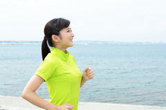 Young woman jogging by the sea Stock Photos
