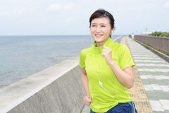 Young woman jogging by the sea Stock Images