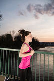 Young woman jogging at sunset. In the city on the bridge cross the river. Girl running outdoors in a city park. Color toned image stock photos