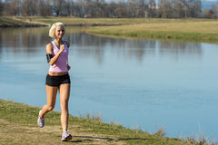 Young woman jogging water park in summer Stock Photography