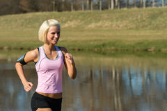 Young woman jogging water park in summer Stock Images