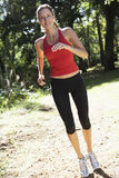 Young Woman Jogging Through Woods Royalty Free Stock Photo