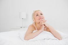 Young woman with joined hands lying in bed Stock Photo