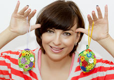 Young woman joking with decorative easter eggs Stock Photos
