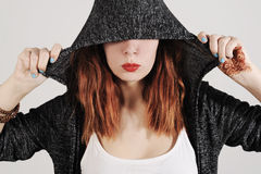Young woman is joking under the hood of her grey jumper. Royalty Free Stock Photography