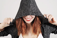 Young woman is joking under the hood of her jumper. Young funny woman is joking under the hood of her grey jumper. Studio shot with a light grey background Royalty Free Stock Photo