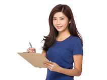 Young woman jot down something on clipboard. Isolated on white background Stock Image