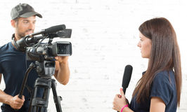 A young woman journalist and a cameraman. A young women journalist with a microphone and a cameraman Stock Images