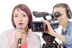 Young woman journalist with a microphone and camerawoman Stock Image