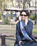 A young woman with a joyful mood communicates on a smartphone in a spring park. Portrait of a young, beautiful woman sitting on a bench in a spring park and stock images