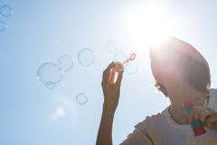 Young woman joyfully blowing a stream of soap bubbles. Stock Photo