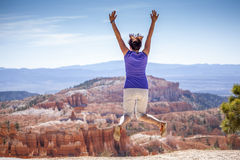 Young woman joyfully jumping in Bryce Canyon Park Stock Photography