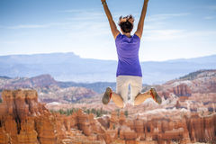 Young woman joyfully jumping in Bryce Canyon Park Royalty Free Stock Photography