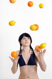 Young  woman  juggling with citrus fruits Stock Images