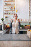 Young woman juggling with fruits at juice bar Royalty Free Stock Photo