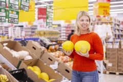 Young woman with juicy melons in the supermarket stock images