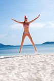 Young woman jump on the beach in santa's hat Stock Photos