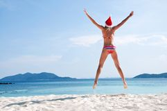 Young woman jump on the beach in santa's hat Stock Image