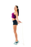 Young woman with jump rope stand sideways in sportswear Stock Images