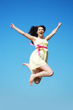 Young woman jumping. A young brunette woman jumping happily in front of a blue sky royalty free stock image