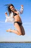 Young woman jumping above water Stock Photo