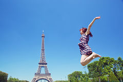 Young woman jumping against Eiffel Tower Stock Images