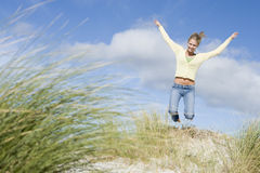 Young woman jumping amongst dunes Royalty Free Stock Photo
