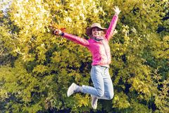 Young woman jumping on the background of autumn foliage royalty free stock image