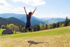 Young woman jumping on a background of mountains Stock Photos
