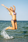 Young woman jumping in the beach Stock Photography