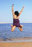 Young woman  jumping in the beach Stock Images