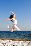 Young woman is jumping in the beach royalty free stock photography
