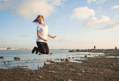 Young woman jumping on the beach Stock Image