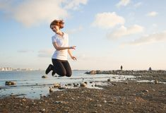 Young woman jumping on the beach Royalty Free Stock Images