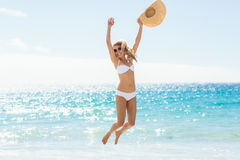 Young woman jumping on beach Stock Images