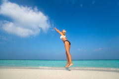 Young woman jumping on the beach, catch cloud Stock Photo