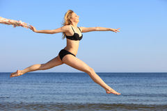 Young woman jumping on beach fit sporty girl Stock Images