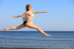 Young woman jumping on beach fit sporty girl Stock Image