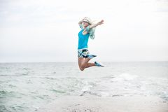 Young woman jumping on the beach. Happy young woman jumping on the beach Royalty Free Stock Photos