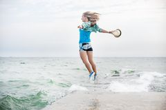 Young woman jumping on the beach. Happy young woman jumping on the beach Stock Photo