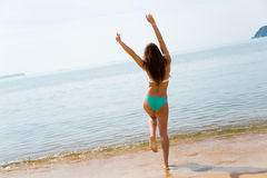 Young woman jumping on the beach Stock Images
