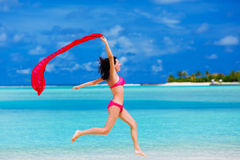 Young woman jumping on the beach with a red scarf royalty free stock photos
