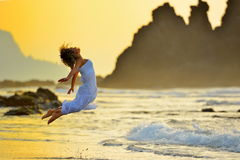 Young woman jumping on the beach in summer Stock Images