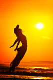 Young woman jumping on the beach in summer Stock Photos