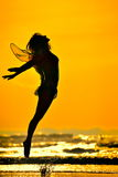 Young woman jumping on the beach in summer evening Stock Images