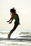 Young woman jumping on the beach in summer sunset Royalty Free Stock Images