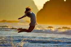 Young woman jumping on the beach in summer sunset Stock Photo