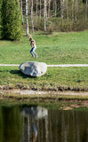 Young woman jumping on the big stone Stock Photography